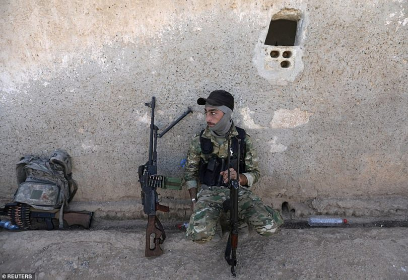 A Turkey-backed Syrian rebel fighter sits with his weapon near the border town of Tel Abyad