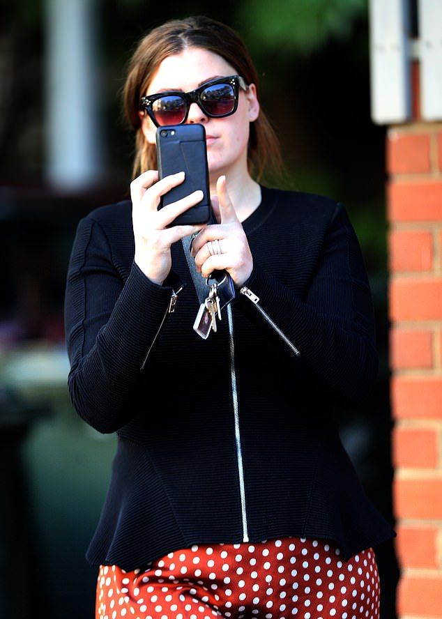Belle Gibson looked indignant at having her photo taken while at school drop-off. She pulled out her phone and fired back