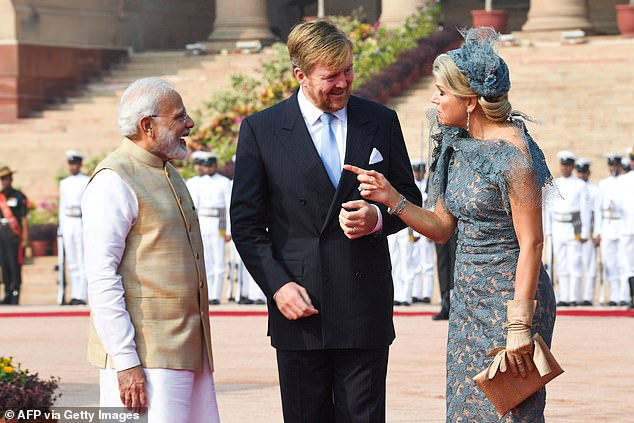 The King donned a white shirt underneath a black suit as he and his wife spoke with the Indian prime minister