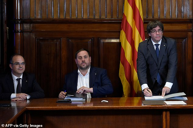 President of the Catalan Government Carles Puigdemont (right) signs a decree calling an independence referendum past in September 2017. Oriol Junqueras (centre) is also pictured at the Catalan Parliament in Barcelona