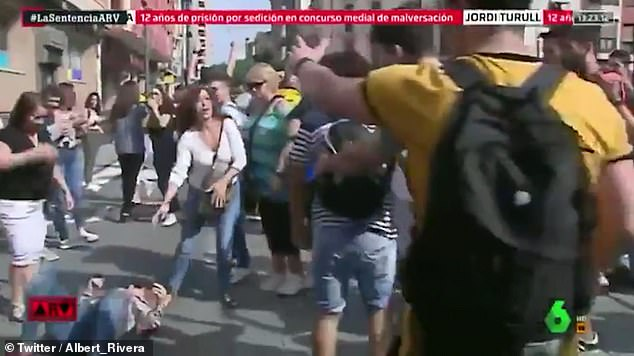 The woman (seen lying on the floor after the attack) was identified asMaria Grima - a militant of far right-wing Spanish party VOX