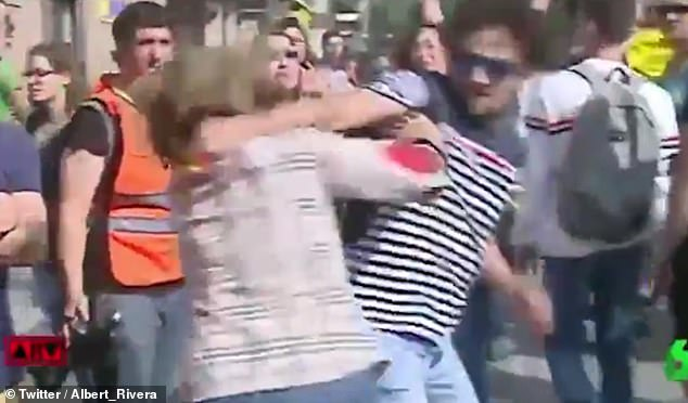 The young man was seen snatching a Spanish flag from a woman goading the crowd of pro-independence protesters before spinning round and smacking her in the head when she tried to retrieve it