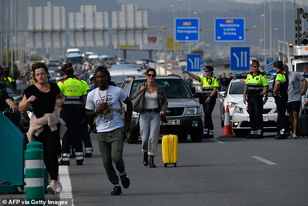 Passengers walking towards El Prat airport as the highway is blocked by Catalan regional police 'Mossos D'Esquadra' officers in Barcelona