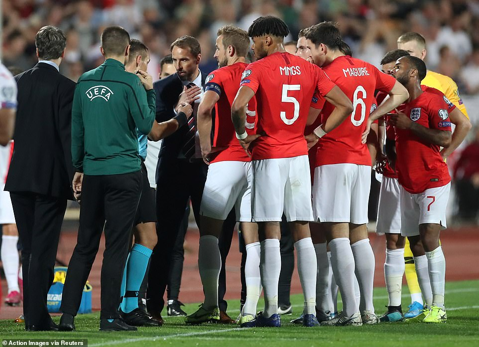 Players and manager Gareth Southgate gather around the match referees to alert them about the horrific abuse the black players were being subjected to