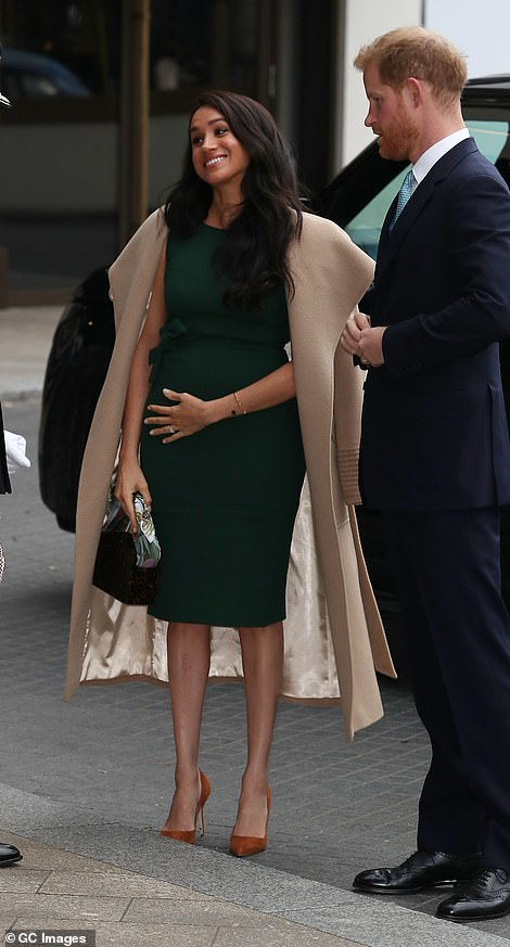 Meghan Markle looked in good spirits as she wore her coat on her shoulders at the awards