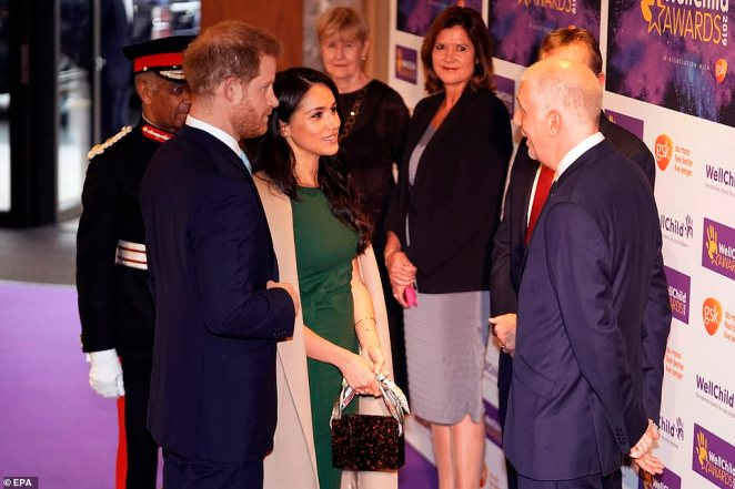 Meghan Markle and Prince Harry are welcomed by officials as they arrive at the WellChild Awards Ceremony in London on Tuesday evening