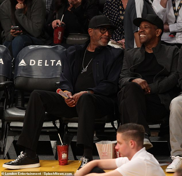 Good spirits: The Training Day star, 64, showcased his on-trend style as he donned a New York Yankees snapback cap for the pre-season game between the Los Angeles Lakers and the Golden State Warriors