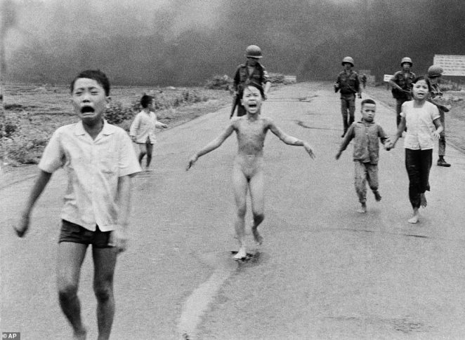 South Vietnamese forces follow after terrified children, including nine-year-old Kim Phuc (centre) as they run down Route 1 near Trang Bang after an aerial napalm attack on suspected Viet Cong hiding places. A South Vietnamese plane accidentally dropped its flaming napalm on South Vietnamese troops and civilians. The terrified girl had ripped off her burning clothes while fleeing. The children (left to right) are: Phan Thanh Tam, younger brother of Kim Phuc, who lost an eye, Phan Thanh Phouc, youngest brother of Kim Phuc, Kim Phuc, and Kim's cousins Ho Van Bon, and Ho Thi Ting. Behind them are soldiers of the Vietnam Army 25th Division