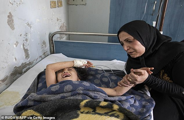 A girl who was injured in the ongoing Turkish offensive against Kurdish-controlled areas of northeastern Syria lying at a hospital in Tal Tamr, near the Syrian Kurdish town of Ras al-Ayn