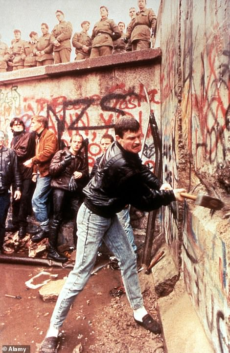 East German guards look on as the Berlin Wall is destroyed in 1989