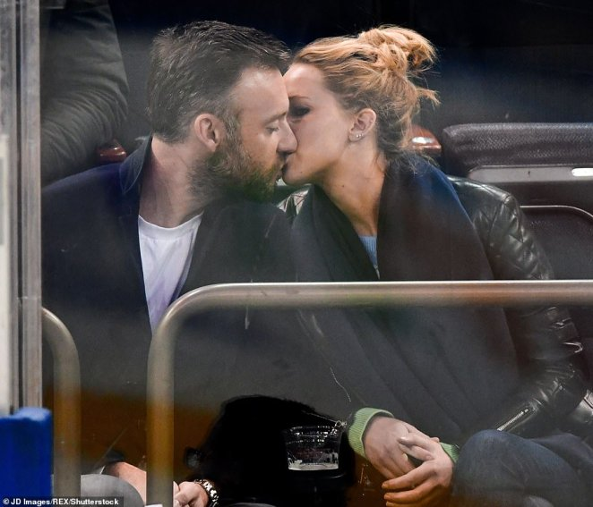 Falling in love: The couple are seen kissing in November last year at an ice hockey match in New York