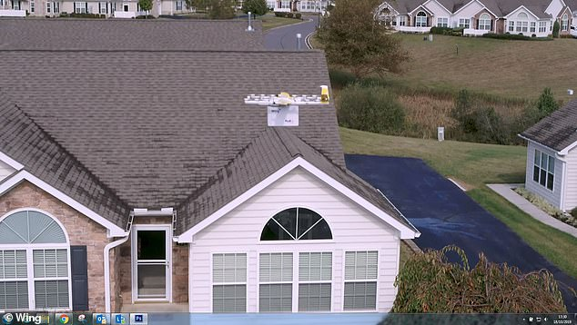 A Wing drone arrives at a home and prepares to lower a package for delivery