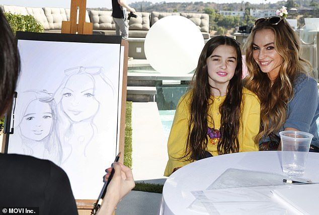Smile! The two girls sit still as an artist sketches their picture to capture the moment