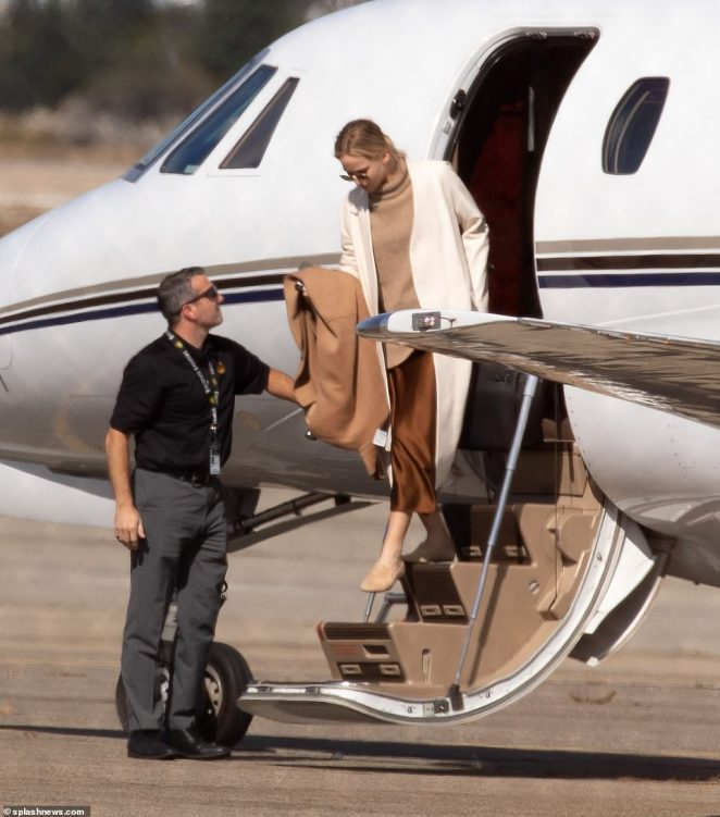 Jennifer wore sunglasses, an oversized camel colored sweater, satin brown skirt and beige flats