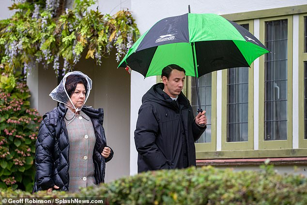 Downpour:Like Tom, she too sought refuge under an umbrella as they continued to film scenes in the drizzly Autumn weather.