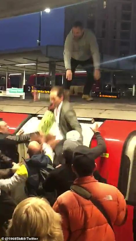 Chaos: XR activist Mark Ovland is dragged off the train by irate commuters at Canning Town station, East London