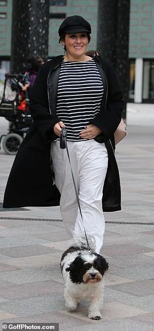 Style: The chat show host donned a black and white striped top with a black coat and white, baggy trousers as she took her dog for a walk