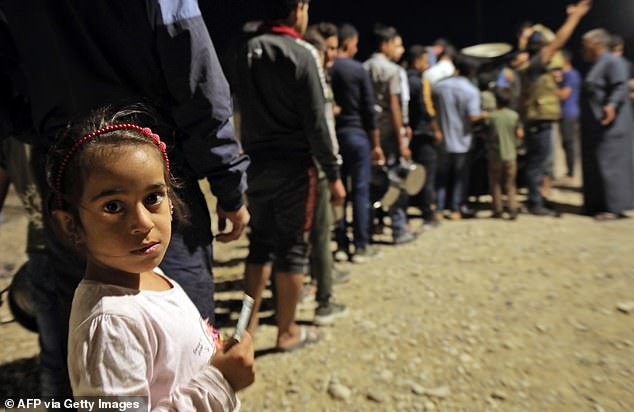 Syrians who were recently turned refugees by the Turkish military operation in northeastern Syria pictured arriving at the Bardarash camp near the Kurdish city of Dohuk on Sunday