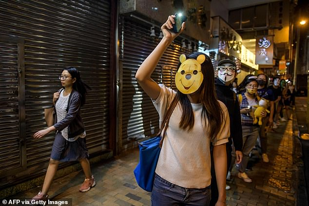 A protester wearing a Winnie the Pooh' mask joins others to form a human chain along a street in Hong Kong on Friday. China has been censoring pictures likening President Xi to Pooh