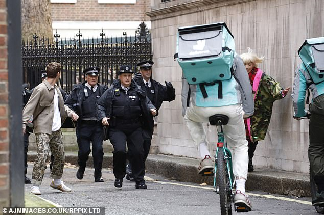 Long arm of the law: Extras dressed as police officers ran in pursuit of the in-character stars
