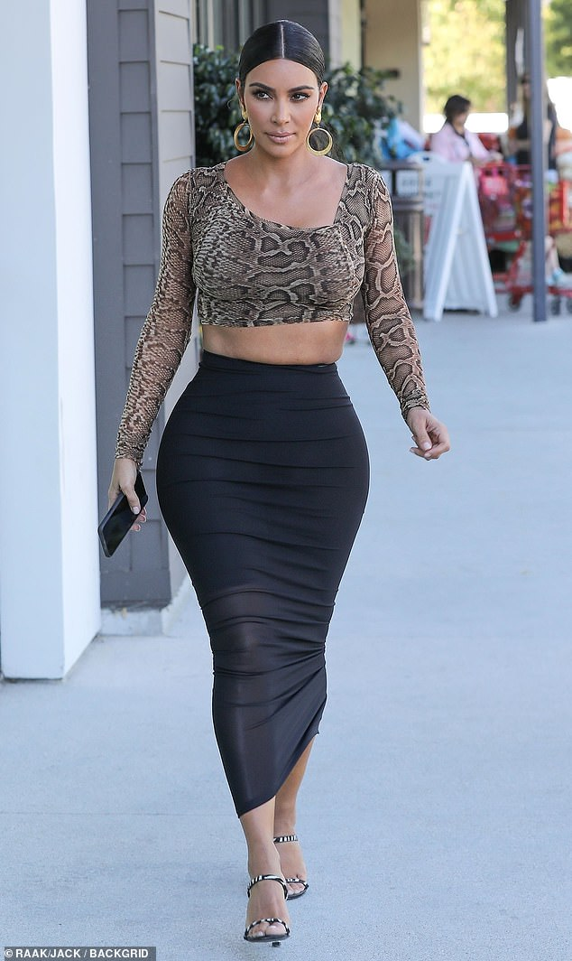 Showstopper: Kim Kardashian stopped by one of her new displays, at an Ulta in Calabasas, on Tuesday and wore a showstopping outfit of a snakeskin top and a figure-hugging black skirt