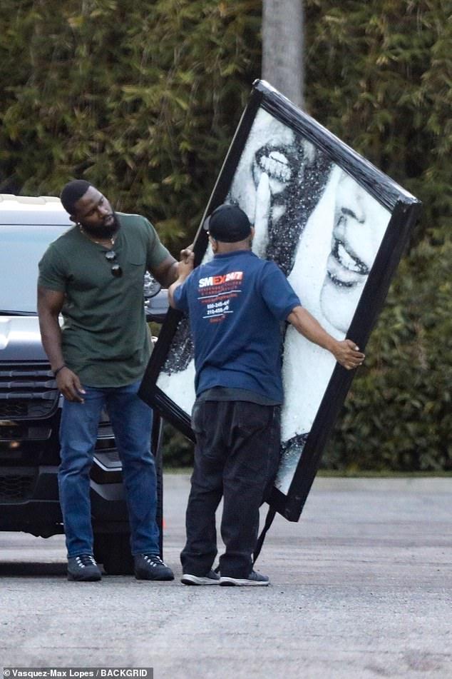 Géant: le livreur semblait avoir du mal à garder la photo au cadre noir alors qu'il la retirait de son camion