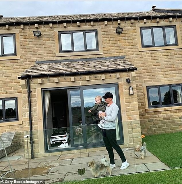 Here, Gary Beadle poses with his son whilst revealing the entire back of his home and garden, including several potential entry points, such as windows and sliding doors which are left ajar