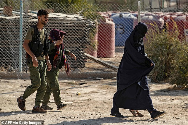 Under guard: Kurdish police accompany women at the camp in northern Syria last week