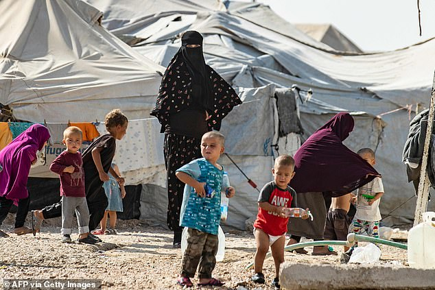 Inmates: Women and children at the al-Hol camp in northern Syria last week where ISIS have seized control amid the chaos of Turkey's invasion