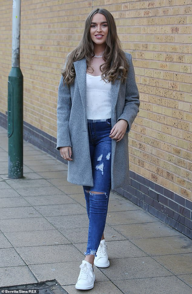 Casually cool: She looked casually cool in ripped jeans and a white top under a grey coat