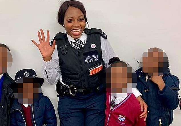 Miss Kareem, who is based in Lambeth, smiles as she poses with a group of schoolchildren
