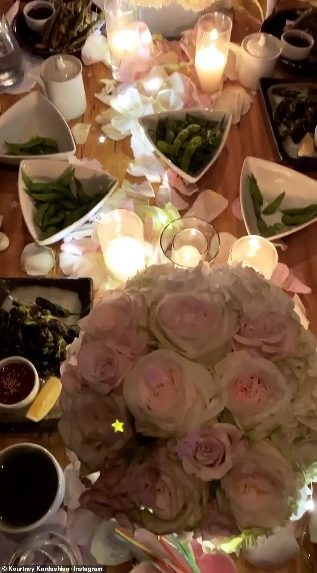 Elegant: The table was festively laid with flowers, candles and party hats, as well as some healthy-looking nibbles for the party guests