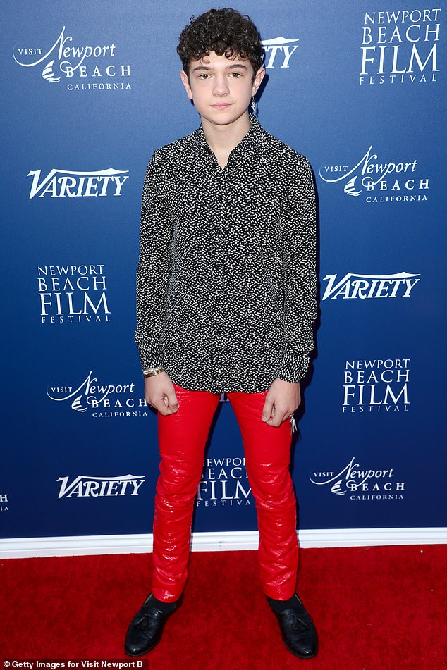 Red leather: Noah Jupe went bold in a black button-down shirt printed in white arrows, paired with some red leather pants