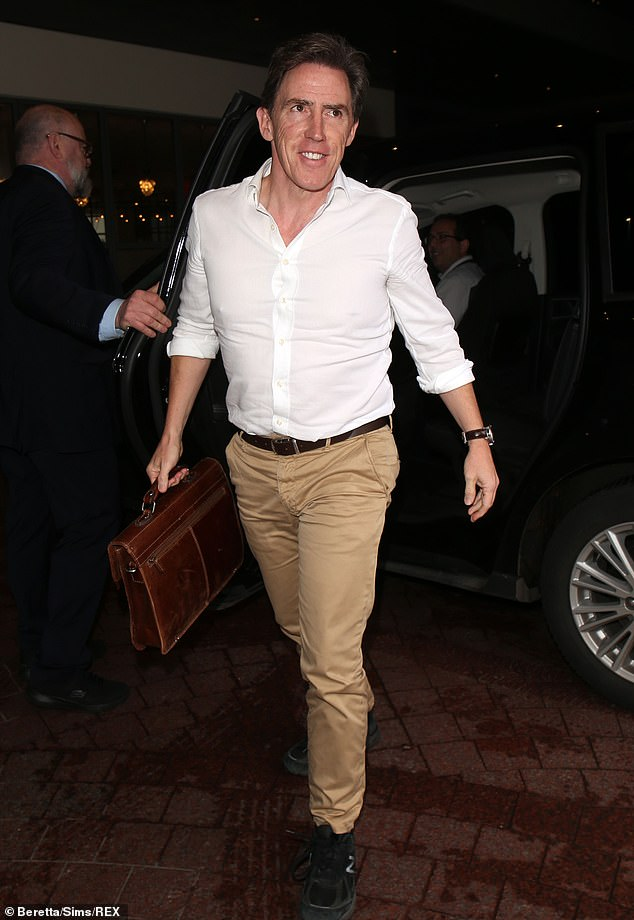 Back in business: Rob strutted along in a white shirt and camel slacks, brandishing a briefcase