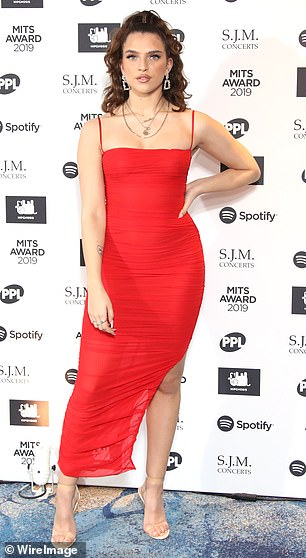 Lady in red: Mae Muller stunned in a clingy ruched midi-dress