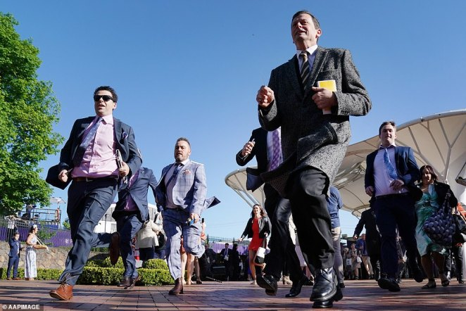 The race is on! A group of men in suits and sunglasses jogged towards the stands and they scrambled for the best view