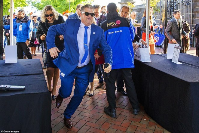 Running wild: One punter in a very bright blue suit flew past the entrance with a glamorous blonde woman behind him