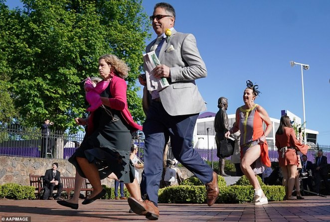 Stretching the legs: Women and men run through Flemington racecourse as excitement builds ahead of the Melbourne Cup