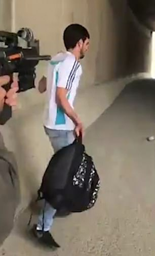 The Palestinian man holds his hands up and starts to calmly walk away
