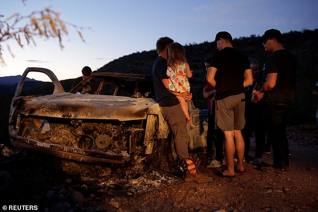 Relatives of slain members of Mexican-American families belonging to Mormon communities observe the burnt wreckage of a vehicle where some of their relatives died in Bavispe