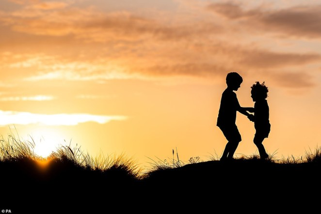 Mr King said: 'Les's photo stood out because of the beautiful composition, with the wooden walkway drawing the eye in and giving that combination of the gentle touch of man in a wild landscape. Pictured: Sarah Gibson's image of children playing at dusk on Knoll's Beach in Dorset