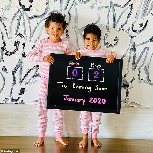 Coming soon! Hope, 34, shared a photo of their sons Hendrix, four, and Legend, three, dressed in pink stripped pajamas while holding up a sign announcing the joyous news