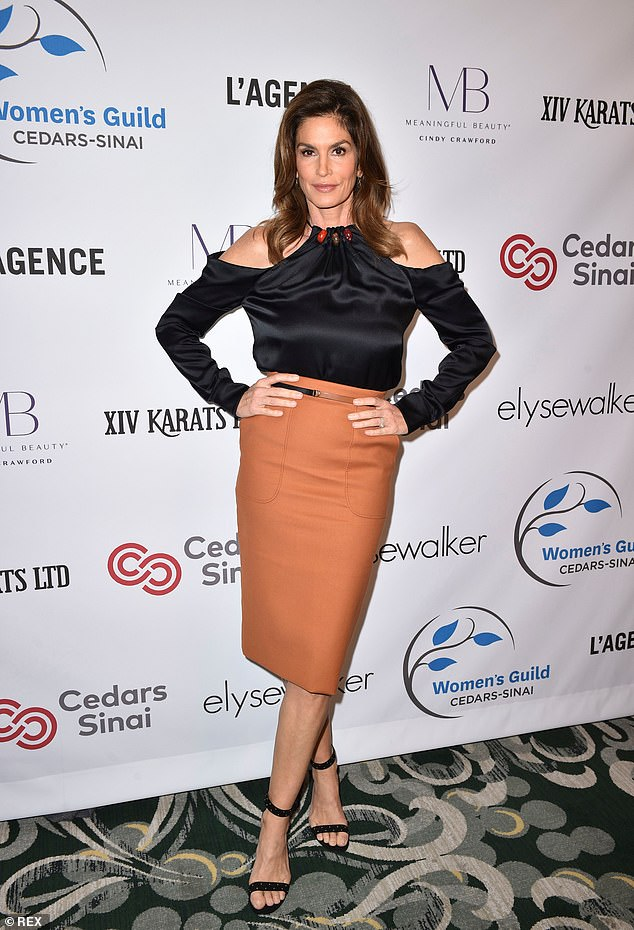 Strike a pose: Crawford worked a caramel hued pencil skirt and silky black blouse