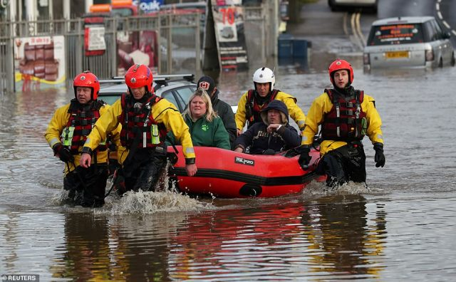 People are ferried to safety through the floodwater this morning by firefighters in Rotherham, South Yorkshire