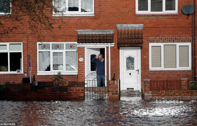 A resident looks out at the floodwater at his doorstep in Bentley, north of Doncaster, in South Yorkshire this morning