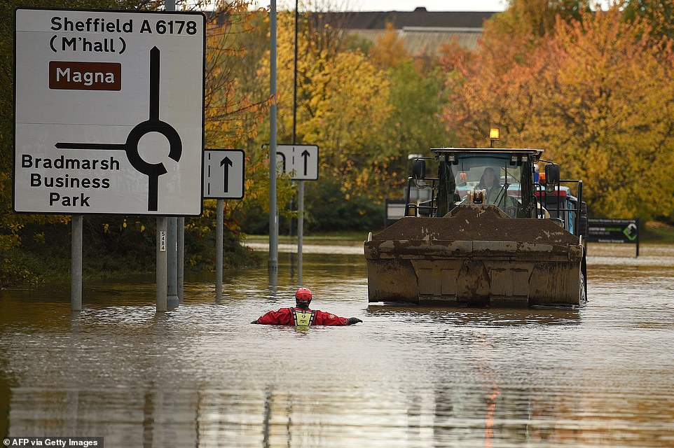 A member of the fire and rescue service wades through flood water as he escorts a JCB towing an truck in Rotherham today