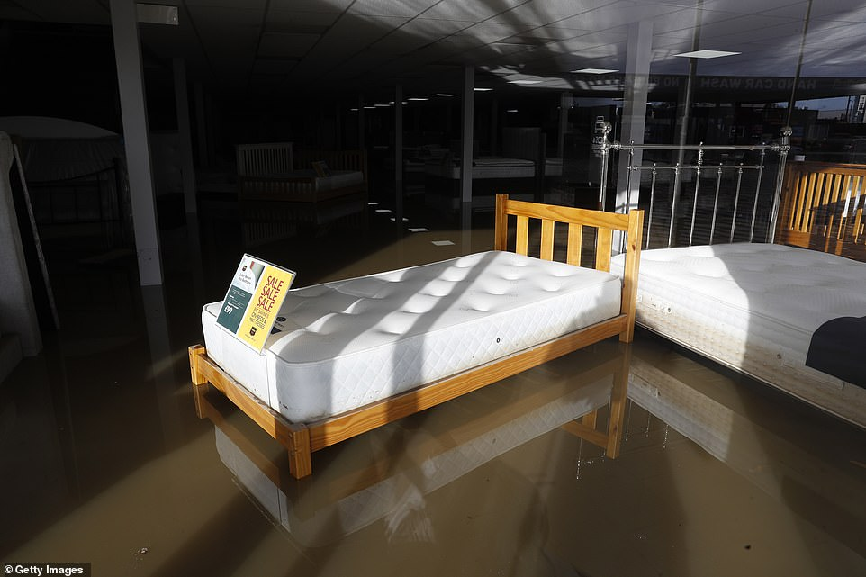 A bed in the window of a shop stands in flood waters after the River Don burst its banks in Rotherham today