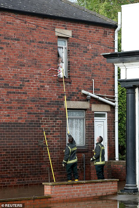 Firefighters provide provisions to an elderly woman in Rotherham