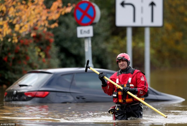 An emergency service worker stands at a flooded road in Rotherham today as the bad weather causes chaos