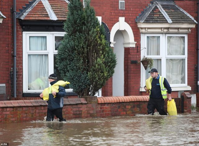 People carrying sandbags on Yarborough Terrace in Doncaster today as parts of England endured a month's worth of rain